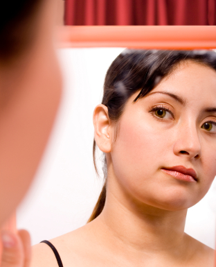 Depressed young woman looking at face in mirror
